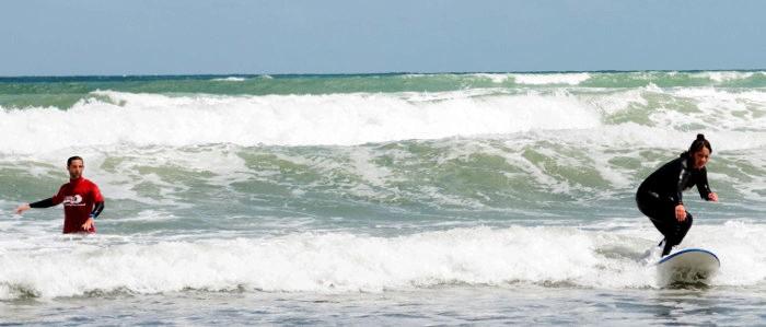 Standing up on beginner surf lesson Raglan